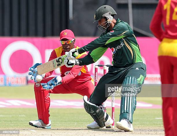 Pakistan's batsman Shoaib Malik in action as Zimbabwe's wicket keeper Richmond Mutumbami looks on during the first of two T20 cricket matches between...
