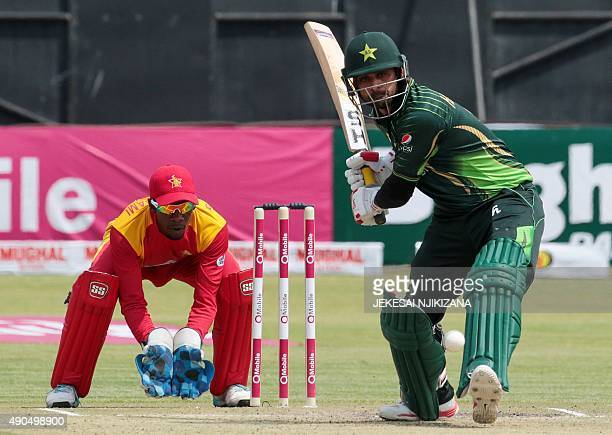 Pakistan's batsman Shoaib Malik prepares to play a shot in front of wicketkeeper Richmond Mutambami during the second of two T20 cricket matches...