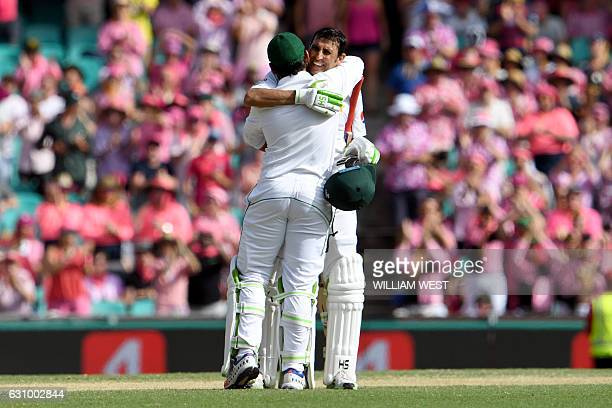 Pakistan's batsman Younis Khan is embraced by teammate Sarfraz Ahmed after scoring his century against Australia during the third day of the third...