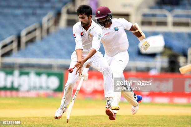 Pakistan's bowler Mohammad Amir stops the ball as West Indies' batsman Shannon Gabriel takes a run on day three of the first Test match between West...