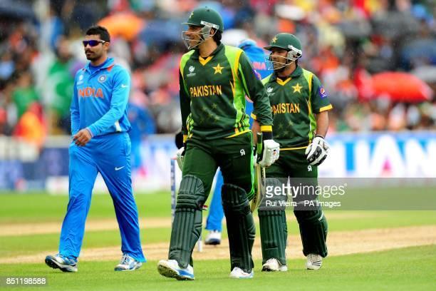 Pakistan's captain MisbahulHaq and Asad Ali walk back to pavillion as rain delays play during the ICC Champions Trophy match at Edgbaston Birmingham