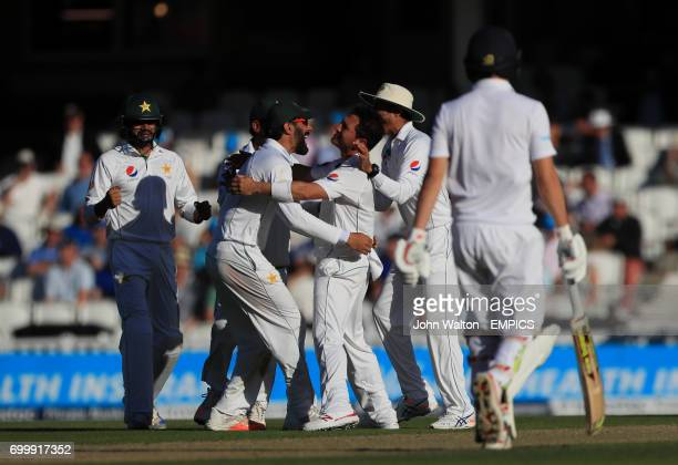 Pakistan's captain MisbahulHaq congratulates bowler Yasir Shah on the wicket of Joe Root for 39