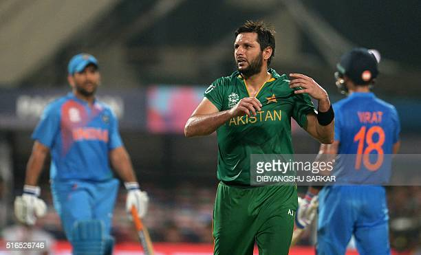Pakistan's captain Shahid Afridireacts as India's captain Mahendra Singh Dhoniand Virat Kohlispeak during the World T20 cricket tournament match...