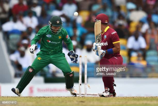Pakistan's captain/wicketkeeper Sarfraz Ahmed celebrates as West Indies' Lendl Simmons is clean bowled off Pakistan's Shadab Khan during the first of...