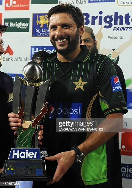 Pakistan's cricket captain Shahid Afridi smiles as he holds the trophy after his team's victory during the second Twenty 20 International cricket...