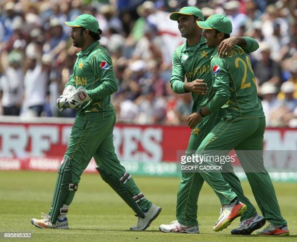 Pakistan's Fakhar Zaman celebrates with Pakistan's Shadab Khan the wicket of England's Moeen Ali as Pakistan's Sarfraz Ahmed walks on during the ICC...