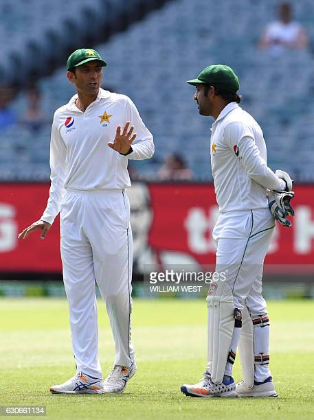 Pakistan's fieldsmen Younis Khan and Sarfraz Ahmed discuss tactics against Australia on the final day of the second cricket Test match in Melbourne...