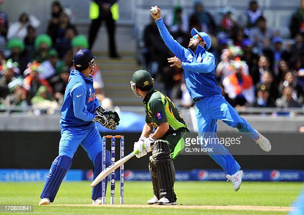 Pakistan's Kamran Akmal turns to watch India's Virat Kohli catch him out for 21 runs during the 2013 ICC Champions Trophy cricket match between...