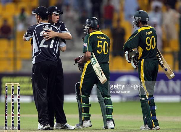 Pakistan's Mohammad Aamir and Saeed Ajmal walk past New Zealand's players as they celebrate after winning the threematch cricket series in Abu Dhabi...
