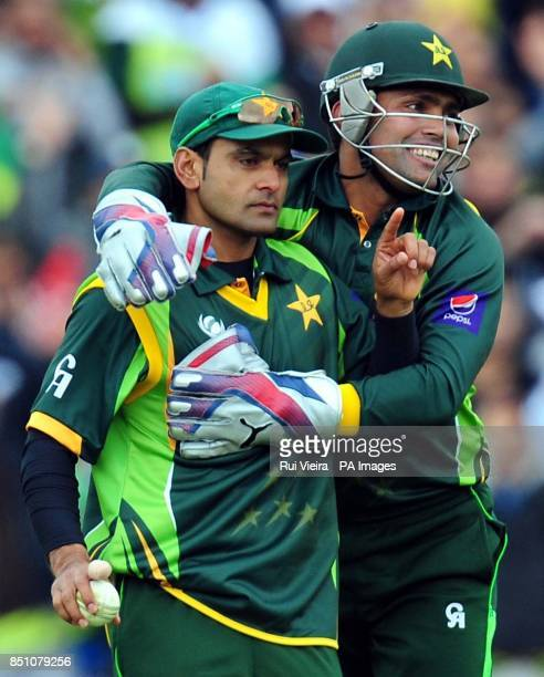 Pakistan's Mohammad Hafeez celebrates with Kamran Akmal after he caught South Africa's Hashim Amla bowled by Pakistan's Saeed Ajmal for 81 during the...