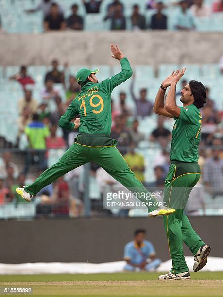 Pakistan's Mohammad Irfan with teammate Ahmed Shehzad celebrate after the dismissal of Sri Lanka's Tillakaratne Dilshan during a practice match...