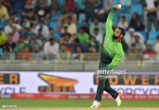 Pakistan's Muhammad Hafeez bowls during the first one day international cricket match between Sri Lanka and Pakistan at Dubai International Stadium...