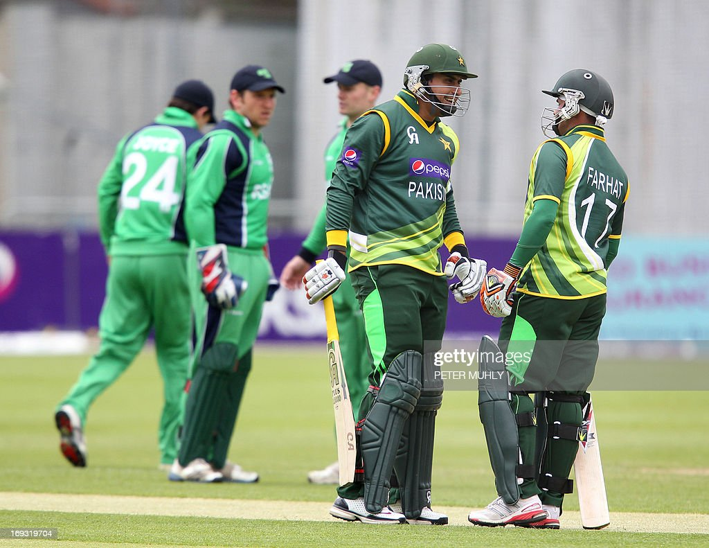 Pakistan's Nasir Jamshaid (L) and Imran Farhat (R) speak before batting during the One Day International (ODI) cricket match between Pakistan and Ireland at Clontarf Cricket Club in Dublin on May 23, 2013. AFP PHOTO/ PETER MUHLY
