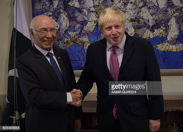 Pakistan's National Security Advisor Sartaj Aziz shakes hands with British Foreign Secretary Boris Johnson prior to their meeting at the Foreign...