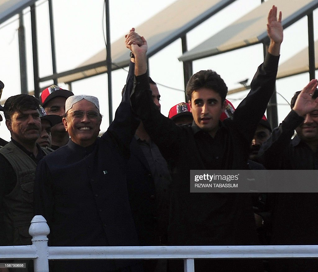 Pakistan's President Asif Ali Zardari (L) widower of assassinated former premier Benazir Bhutto, waves with his son and chairman of ruling Pakistan People's Party (PPP) Bilawal Bhutto (R) to supporters outside the Bhutto family mausoleum in Garhi Khuda Bakhsh on December 27, 2012, on the fifth anniversary of the assassination of Benazir Bhutto. The son of Pakistan's slain former prime minister Benazir Bhutto launched his political career on the anniversary of his mother's death with an attack on the country's judiciary. More than 200,000 people gathered at the Bhutto family mausoleum in Garhi Khuda Bakhsh in the southern province of Sindh to pay their respects to Benazir and to hear Bilawal Bhutto Zardari make his first major public speech.