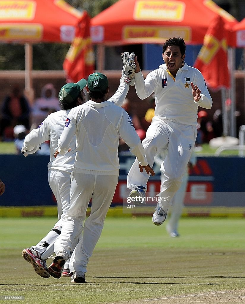 Pakistan's Saeed Ajmal celebrates the dismissal of unseen South African cricketer Alviro Petersen for 17 runs during the 2nd Test between South Africa and Pakistan , in Cape Town at Newlands on February 15, 2013.