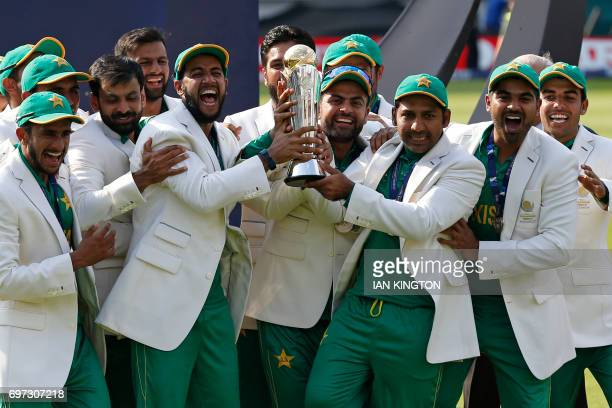 Pakistan's Sarfraz Ahmed holds the trophy as Pakistan players celebrate their win at the presentation after the ICC Champions Trophy final cricket...