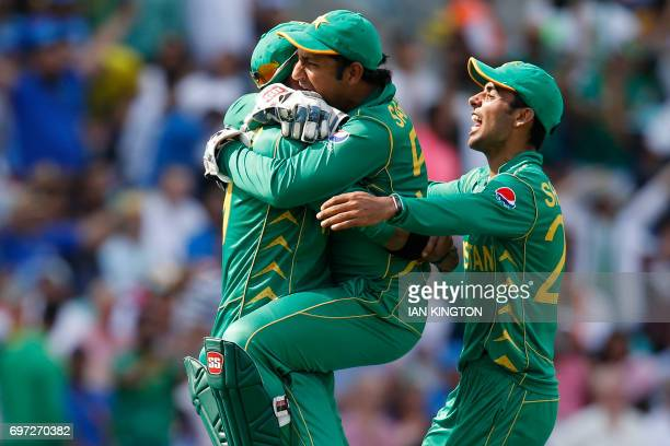 Pakistan's Shadab Khan and Pakistan's Sarfraz Ahmed celebrate with Pakistan's Imad Wasim after he catches India's MS Dhoni during the ICC Champions...