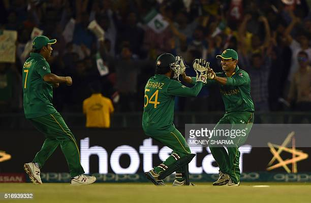 Pakistan's Sharjeel Khan celebrates with Pakistan's Sarfaraz Ahmed after the dismissal of New Zealand's Colin Munro during the World T20 cricket...