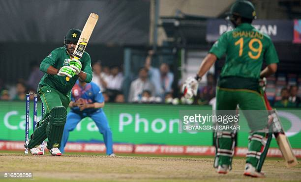 Pakistan's Sharjeel Khan plays a shot as Pakistan's Ahmed Shehzad looks on during the World T20 cricket tournament match between India and Pakistan...