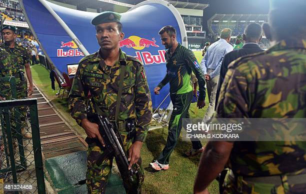Pakistan's Shoaib Malik walks past security forces as he and teammates walk off the field after clashes between supporters of both sides during the...