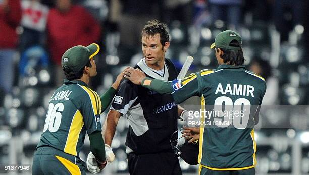 Pakistan's Umar Akmal and Mohammad Aamir congratulate New Zealand's Grant Elliott at the end of ICC Champions Trophy 2nd semifinal between Pakistan...