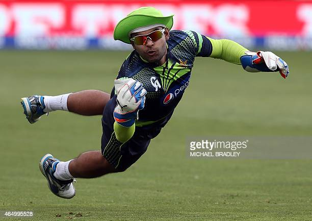 Pakistan's Umar Akmal makes a catch during during a training session ahead of their 2015 Cricket World Cup Group B match against United Arab Emirates...