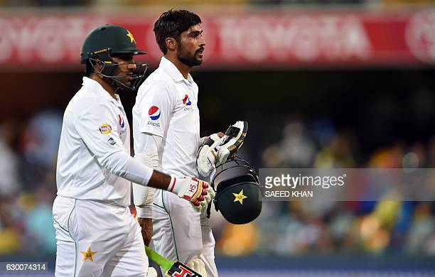 Pakistan's unbeaten pair Sarfraz Ahmed and Mohammad Amir walk back to pavilion at the end of play during the second day of the daynight cricket Test...