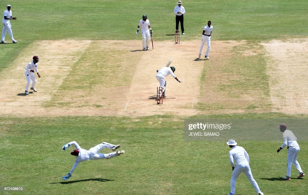 Pakistan's Wahab Riaz (C) is bowled off West Indies' bowler Alzarri Joseph (top-R) on day four of the first Test match between West Indies and Pakistan at the Sabina Park in Kingston, Jamaica, on April 24, 2017. / AFP PHOTO / Jewel SAMAD