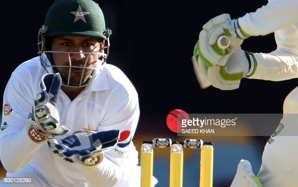 TOPSHOT Pakistan's wicketkeeper Sarfraz Ahmed eyes the ball as Australia's batsman Steven Smith plays a shot during the third day of the daynight...