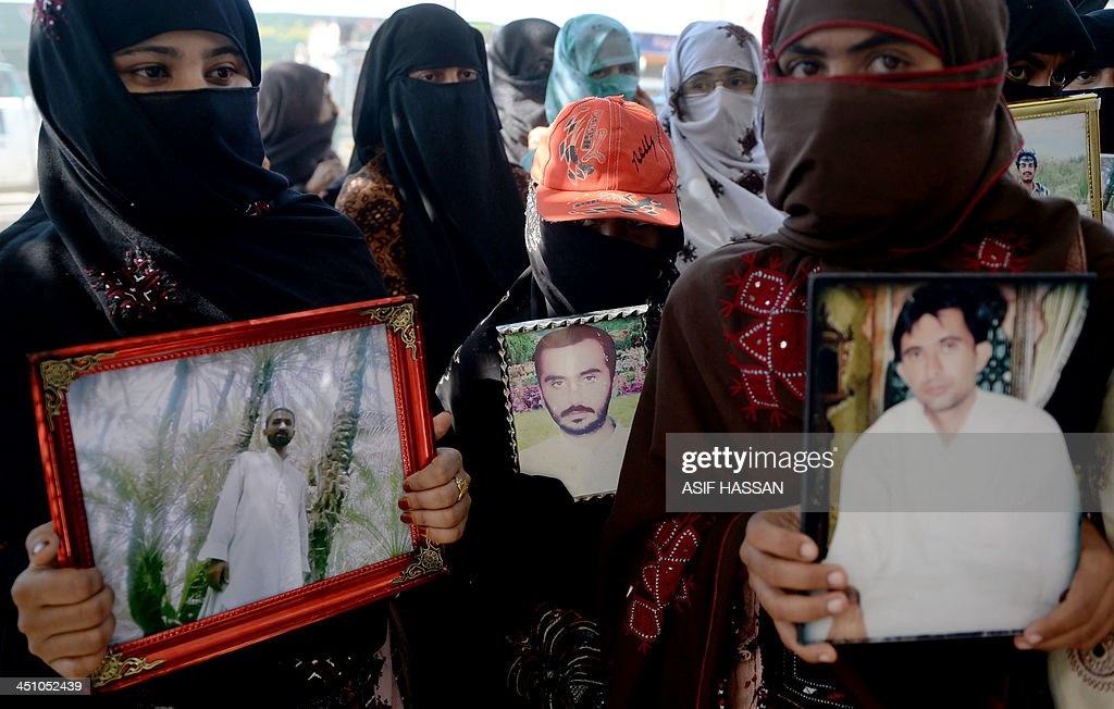 STORY 'Pakistan-unrest-rights-missing' by Ashraf KHAN Pakistani Baloch women carry photographs of missing ethnic Balochs at Hub district as they march towards Karachi from Quetta, the capital of Baluchistan Province on November 21, 2013. After 700 gruelling kilometres of walking across scorched, arid plains, some two dozen women from Pakistan's troubled southwestern Baluchistan province are nearing the end of their march to seek justice for missing loved ones. For nearly a month they have walked for brothers, sons and husbands who have disappeared, allegedly at the hands of Pakistan's security services. AFP PHOTO/Asif HASSAN