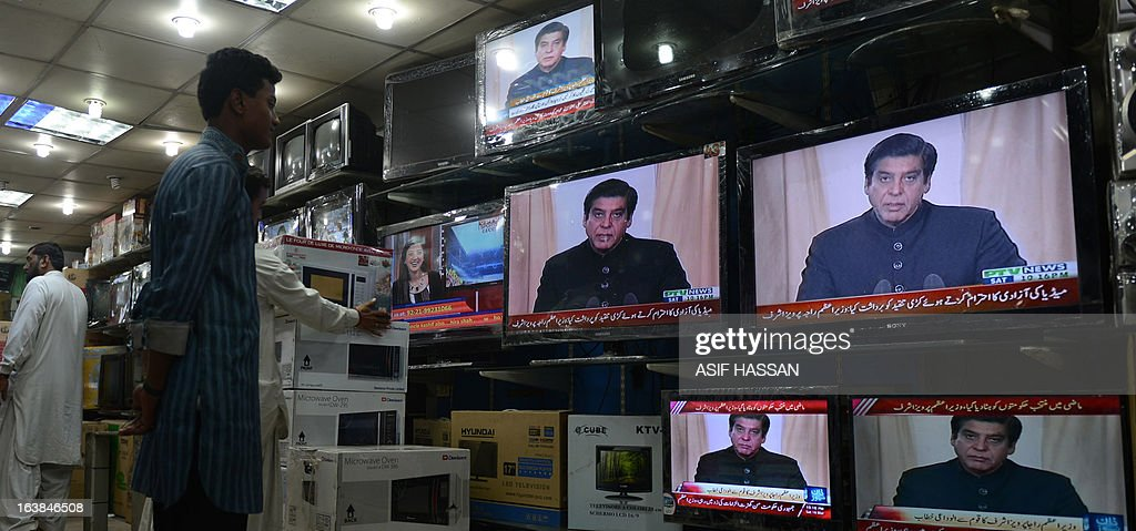 Pakistan-unrest-vote-government,FOCUS by Sami Zubeiri Pakistanis listen to Pakistani Prime Minister Raja Pervez Ashraf's address to the nation on national television at a shop in commercial center in Karachi on March 16, 2013. Pakistan's parliament has become the first in history to complete a full term in office, but a raft of key achievements have been overshadowed by mismanagement, economic decline and worsening security. AFP PHOTO/ ASIF HASSAN