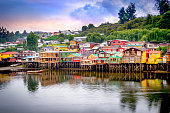 Palafitos in Castro. Castro is the capital of Chiloe Province, in the Los Lagos Region, Chile. Palafitos are houses raised on piles over the surface of the soil or a body of water