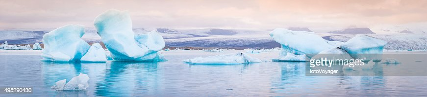 Pale blue icebergs floating in tranquil Arctic ocean lagoon Iceland