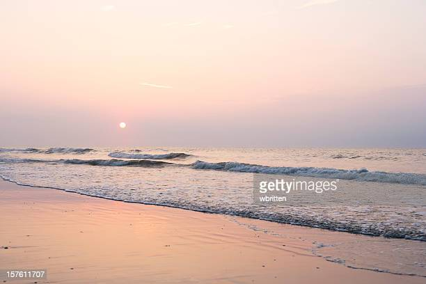 Pale sunrise over ocean waves
