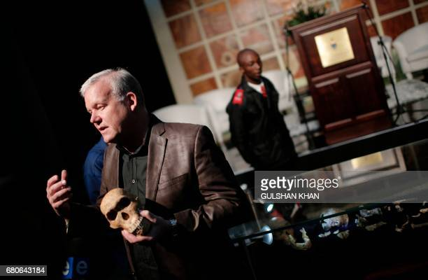 Paleoanthropologist and National Geographic ExplorerinResidence Professor Lee Rogers Berger holds a replica of the skull of 'NEO' a new skeleton...