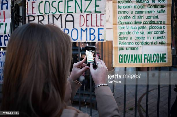 Palermo Dec 20 2013 A girl is photographing a board with a smartphone in memory of magistrate Giovanni Falcone killed by the Mafia People...