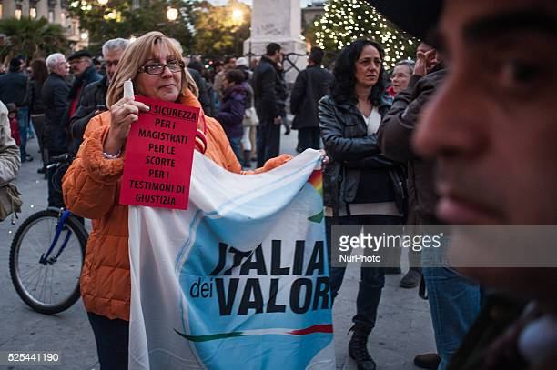 Palermo Dec 20 2013 A woman is holding a protest board and the flag of the political party 'Italia dei Valori' People demonstrated to show support...