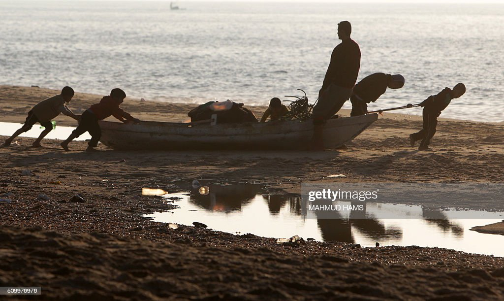 Palestian children help their father to get a boat in the water at the beach in Deir al-Balah, in central Gaza, on February 13, 2016. / AFP / MAHMUD HAMS