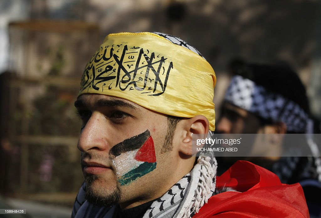 A Palestian wearing the trademark chequerred keffieyh with a national flag painted on his face, attends a rally in support of president Mahmud Abbas's Farah party on January 4, 2013 in Gaza City. The rally was the first in Gaza since Hamas seized control of the territory in 2007, marking the 48th anniversary of Fatah taking up arms against Israel.
