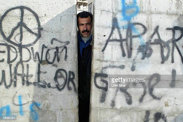 A Palestinain looks through a gap between the blocks of Israel's controversial barrier that is still under construction January 9 2004 in the...