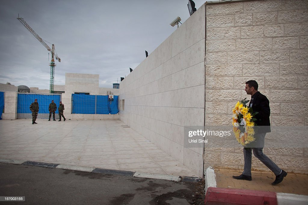 A Palestinan man arrives at the mausoleum of Yasser Arafat carrying a wreath on November 27, 2012 in Ramallah, West Bank. A team of investigators last night exhumed and reburied the body of former Palestinian leader Yasser Arafat in a bid to determine whether he was murdered by radiation poisoning. The new probe comes after traces of the deadly radioactive isotope, polonium-210, were found on his clothing. Arafat died of unexplained causes in a French hospital in November 2004.