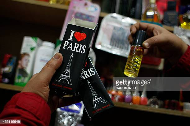 A Palestinan man holds a bottle of perfume with a drawing of the Eiffer Tower on the box in Khan Younis in the southern Gaza Strip on December 11...