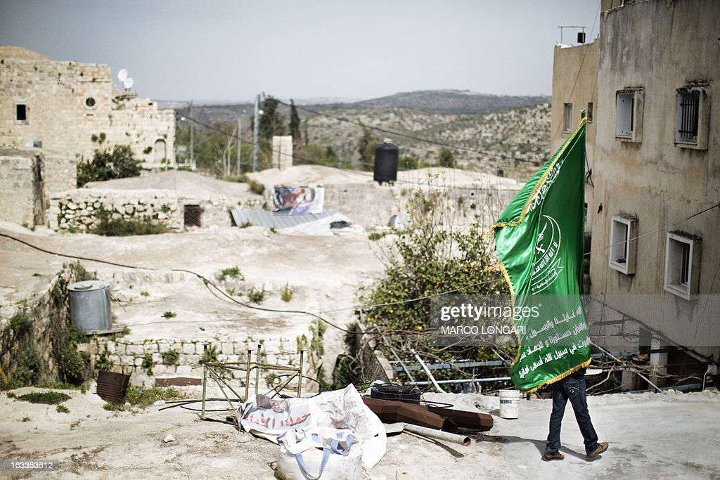 A Palestinan mourner carries the flag of the radical Islamic movement Hamas during the funeral of Mohammad Asfour in the West Bank village of Abud on March 8, 2013. Asfour died of his wounds on March 7, after he was hit in the head two weeks ago by a rubber-coated steel bullet during a demonstration over the death of a Palestinian prisoner in Israeli custody.