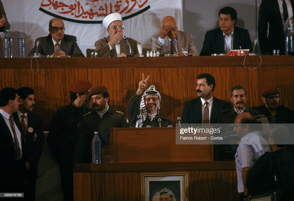 Palestine Liberation Organization leader Yasser Arafat gives the peace sign at the Palestinian National Council. The PLO proclaimed the state of Palestine, acknowledged resolutions 181, 242, and 338, and condemned terrorism during the meeting. Behind Arafat (2nd from the left) is Sheikh Abdel Hamid As-Sayeh, President of the Palestinian National Council.