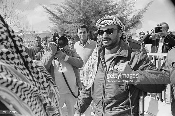 Palestine Liberation Organization leader Yasser Arafat shoulders an AK47 while members of the media follow him as he arrives at a press conference in...