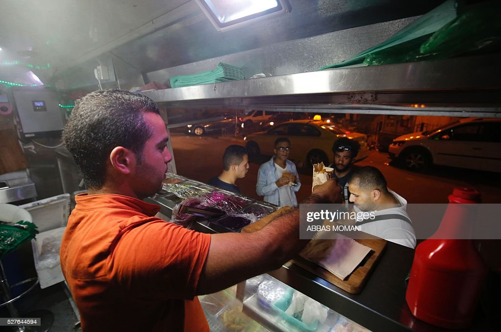 Palestinian Abderrahman serves food to customers at his food truck called 'Food Train' which he runs with his friend Khuldun in the West Bank city of Ramallah on May 3, 2016. The idea for the first food truck authorised to operate in the Palestinian territories was born in an Israeli prison, where Khaldun al-Barghuthi and Abderrahman al-Bibi served food to their fellow inmates. EZZEDINE