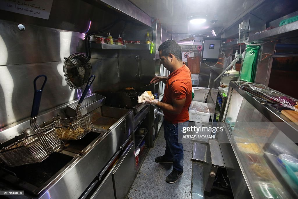 Palestinian Abderrahman prepares food to customers at his food truck called 'Food Train' which he runs with his friend Khaldun in the West Bank city of Ramallah on May 3, 2016. The idea for the first food truck authorised to operate in the Palestinian territories was born in an Israeli prison, where Khaldun al-Barghuthi and Abderrahman al-Bibi served food to their fellow inmates. EZZEDINE