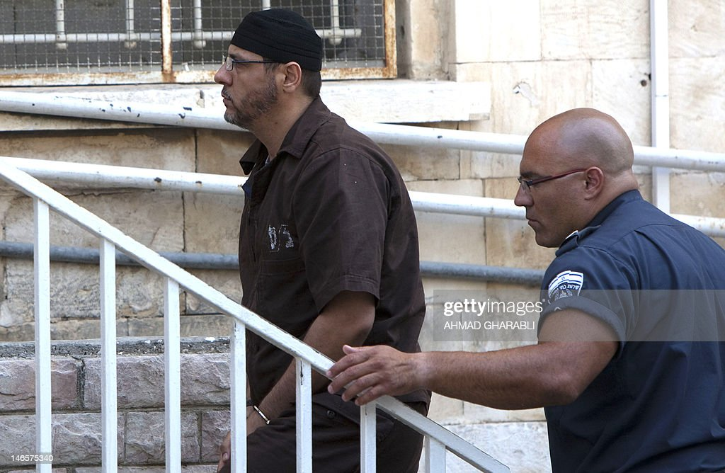 Palestinian Abdullah Barghouti, a leading commander for the Ezzedine al-Qassam Brigades, the armed wing of Hamas in the West Bank, is escorted by Israeli police into the Magistrate's Court for a hearing in Jerusalem on June 20, 2012. Barghouti is currently serving 67 life-term sentences in Israeli prison.