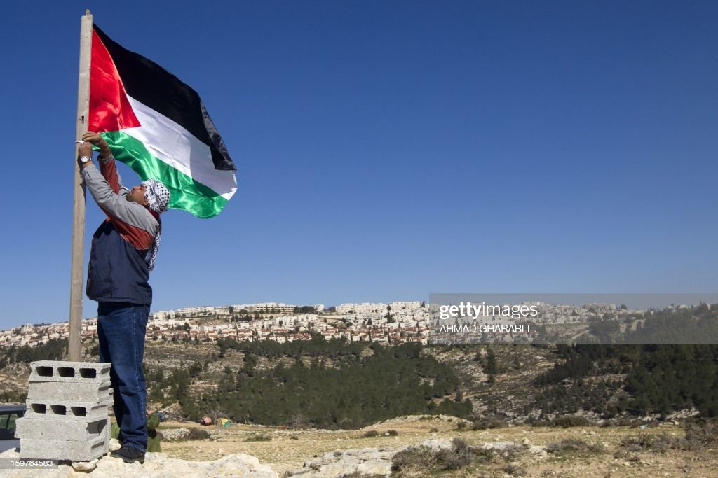 A Palestinian activist fixes a flag near the newly erected encampment set up to protest against Israel's intention to confiscate land on January 20, 2013 in the West Bank village of Beit Iksa. Activists say the Israeli army recently announced it would confiscate over 500 dunams (124 acres, 50 hectares) of land by the village, located on the northwestern outskirts of Jerusalem. On the background is seen the Israeli settlement of Ramot. AFP PHOTO/AHMAD GHARABLI